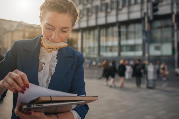 La mujer ocupada tiene prisa, no tiene tiempo, va a comer bocadillos mientras viaja. trabajador comiendo, tomando café, hablando por teléfono, al mismo tiempo. empresaria haciendo múltiples tareas.