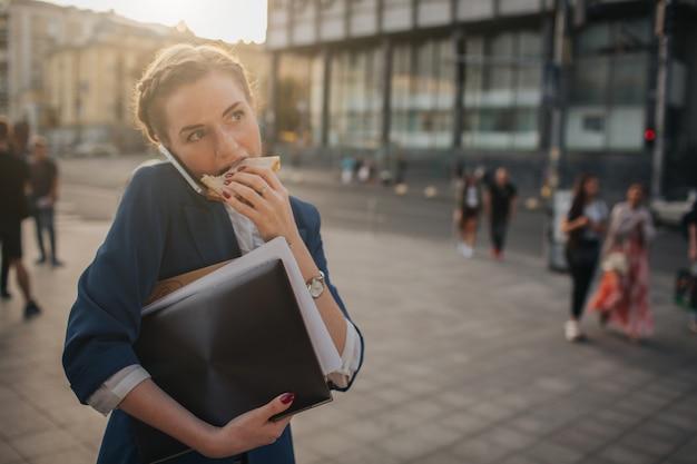 La mujer ocupada tiene prisa, no tiene tiempo, va a comer bocadillos mientras viaja. trabajador comiendo, tomando café, hablando por teléfono, al mismo tiempo. . persona de negocios multitarea.