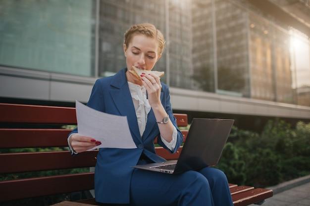 La mujer ocupada tiene prisa, no tiene tiempo, va a comer un refrigerio al aire libre. trabajador comiendo y trabajando con documentos en la computadora portátil al mismo tiempo. empresaria haciendo múltiples tareas. mult.