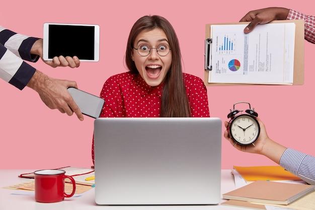 Mujer ocupada usa anteojos, tiene exceso de trabajo, tiene fecha límite para preparar la tarea, está rodeada de computadora portátil, las manos sostienen dispositivos electrónicos