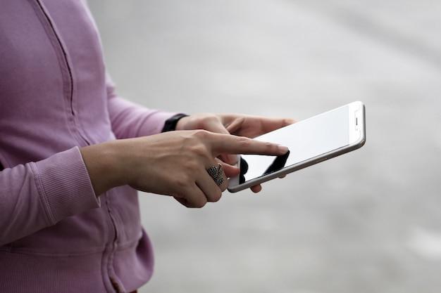 Una mujer está ocupada usando un teléfono celular.