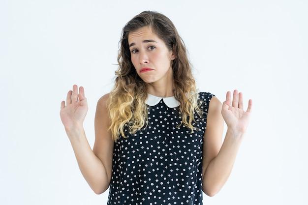 Mujer ofendida mirando a la cámara y levantando las manos. concepto de ofensa