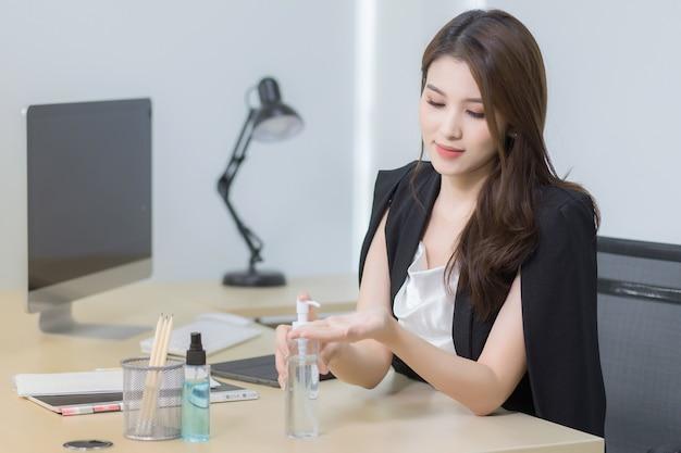 Mujer de oficina asiática está sentada y presionando un gel de alcohol para lavarse las manos felizmente en el trabajo