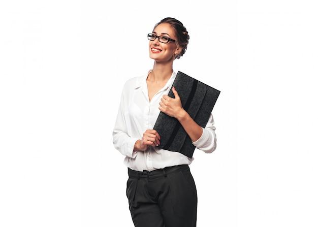 Mujer de oficina joven bastante rubia abrazando una carpeta de documentos gris y sonriendo