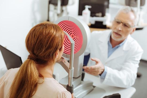 Mujer y oftalmóloga. mujer joven pelirroja con cola de caballo sentada frente al oftalmólogo