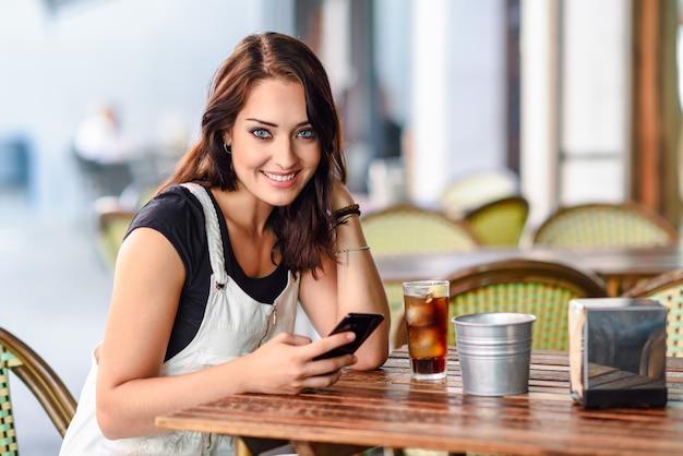 Mujer con ojos azules sentada en café urbano usando teléfono inteligente