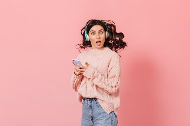 Mujer con ojos azules con sorpresa mira a cámara sobre fondo rosa. chica en suéter de punto escucha música en auriculares y sostiene el iphone.
