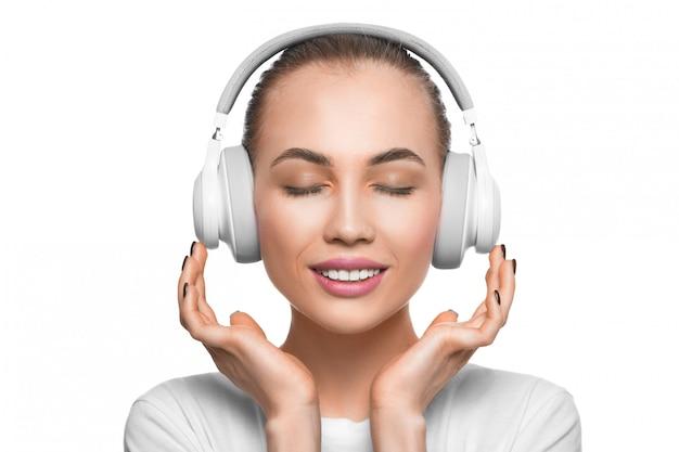 Mujer con los ojos cerrados en auriculares escuchando la música.