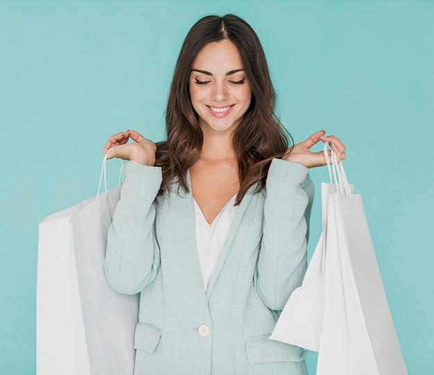 Mujer con los ojos cerrados y bolsas de compras en ambas manos.