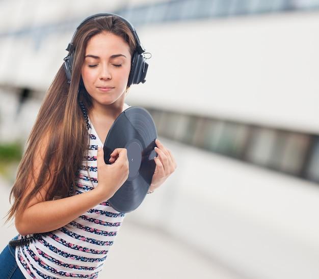 Mujer con los ojos cerrados y un disco de vinilo