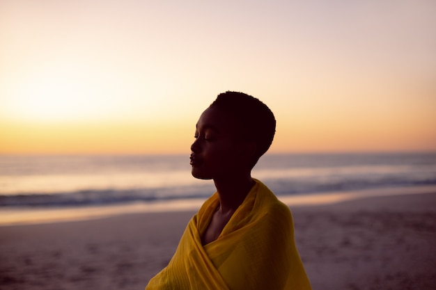 Mujer con los ojos cerrados envuelta en un pañuelo amarillo en la playa