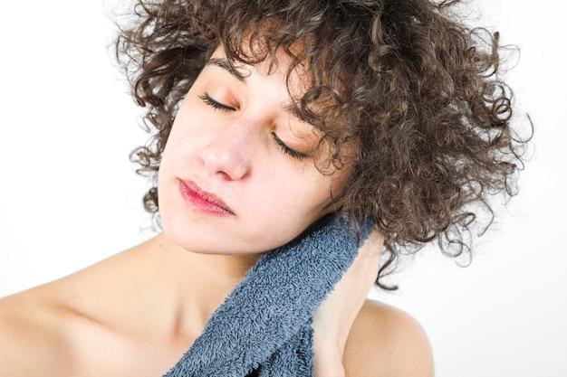 Mujer con los ojos cerrados limpiándose con una toalla