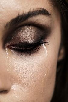 Mujer con ojos cerrados y maquillaje llorando