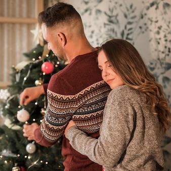 Mujer con los ojos cerrados que abrazan al hombre de atrás en suéteres cerca del árbol de navidad