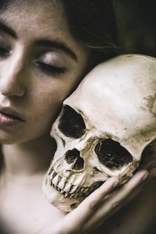 Mujer con los ojos cerrados, sosteniendo el cráneo