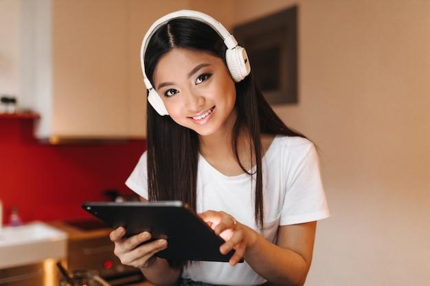 Mujer de ojos marrones con auriculares masivos mira al frente, sonríe y sostiene la tableta