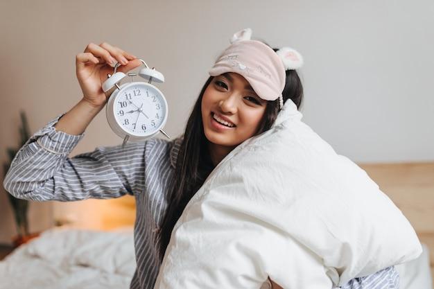 Mujer de ojos marrones en pijama azul y antifaz rosa posa con reloj despertador en la cama