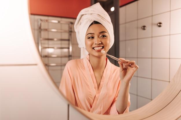Mujer de ojos marrones en toalla blanca se cepilla los dientes
