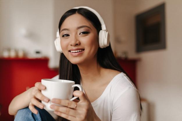 Mujer de ojos marrones en top blanco sosteniendo la taza y posando con una sonrisa