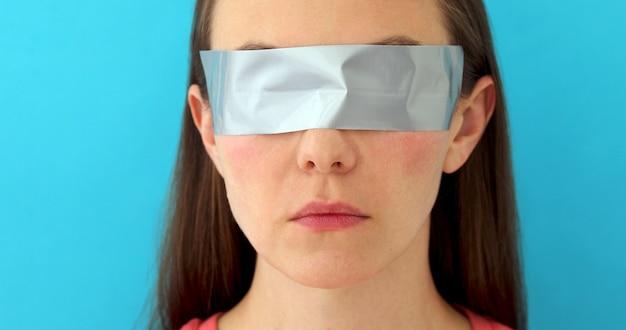 Mujer con ojos pegados con tira de cera