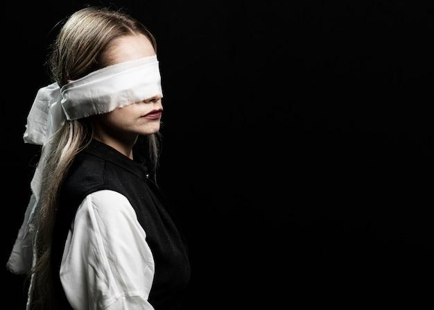 Mujer con los ojos vendados y copia espacio