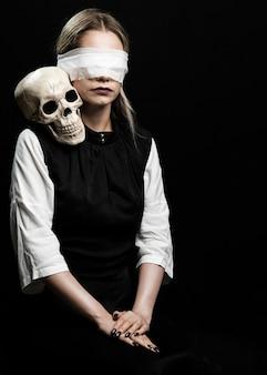 Mujer con los ojos vendados y cráneo humano