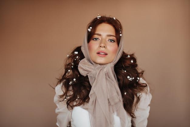 Mujer de ojos verdes en blusa blanca y con pequeñas flores en el pelo posando. mujer con pañuelo en la cabeza mira a la cámara.
