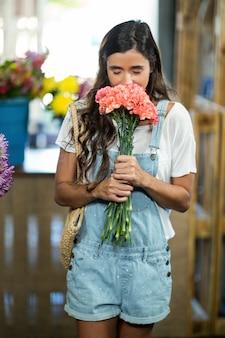 Mujer oliendo un ramo de flores