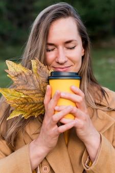 Mujer oliendo su café mientras sostiene algunas hojas