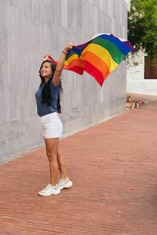 Mujer ondeando la bandera lgtb en la ciudad. concepto lgbt