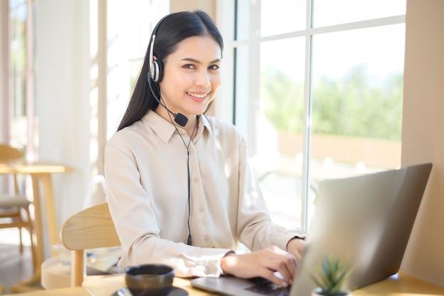 Una mujer de operador de servicio al cliente en el auricular usando la computadora respondiendo la llamada del cliente en la oficina