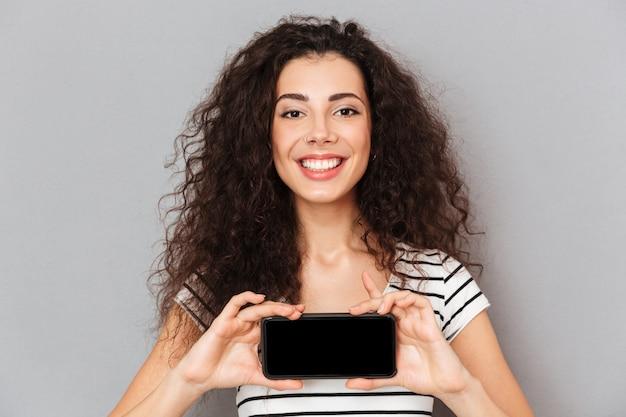Mujer optimista con anillo en la nariz sosteniendo su teléfono móvil, lo que significa una buena elección sonriendo mientras está aislado contra la pared gris de cerca
