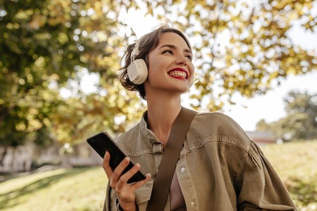 Mujer optimista con cabello morena en ropa de mezclilla oliva sonríe y sostiene el teléfono afuera. mujer en auriculares ligeros posa al aire libre.