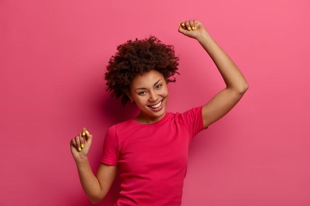 Una mujer optimista se enfría en el interior, mantiene los brazos en alto, aprieta los puños y baila sin preocupaciones