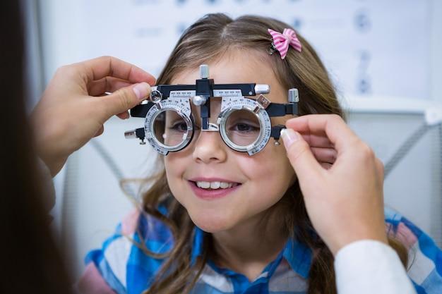 Mujer optometrista examinando paciente joven con marco de prueba