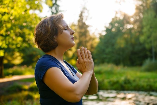 Mujer en oración en la naturaleza al atardecer en el parque