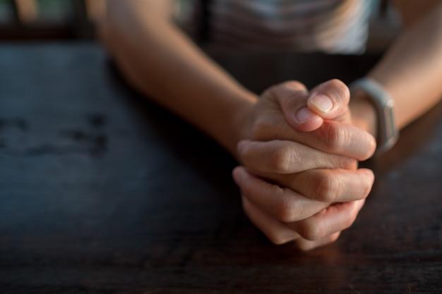 Mujer orando en la mañana, con las manos juntas en oración.