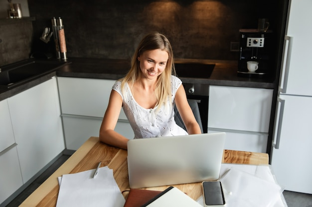 Mujer con ordenador portátil trabajando en la oficina en casa