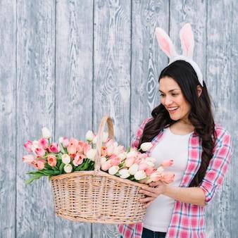 Mujer con orejas de conejo blanco mirando canasta de tulipanes contra tablón de madera gris