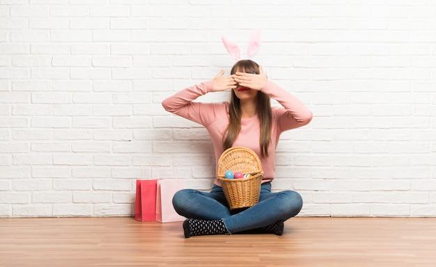 Mujer con orejas de conejo para las vacaciones de semana santa sentadas en el suelo cubriendo los ojos con las manos