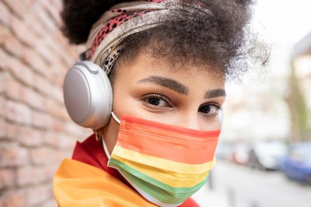 Mujer, orgullo gay, bandera y auriculares lleva una mascarilla con los colores del arco iris
