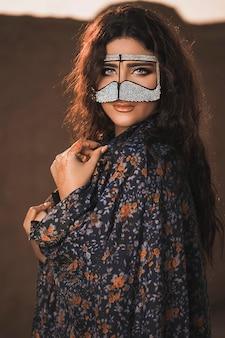 Mujer oriental en chal y mascarilla con diamantes
