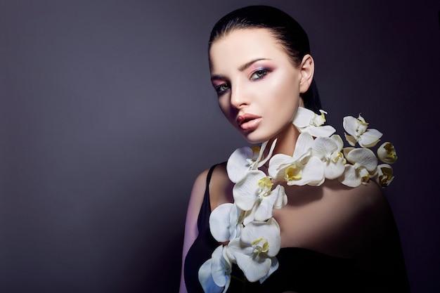 Mujer con orquídea blanca cerca de la cara