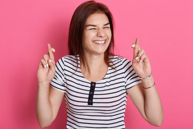Una mujer oscura y esperanzada se siente afortunada, cruza los dedos, espera el milagro, pide deseos y tiene grandes esperanzas, sonríe ampliamente, usa una camiseta a rayas, posa contra la pared de rosas.