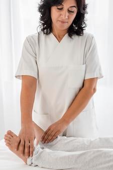 Mujer osteópata tratando las piernas de un paciente en el hospital