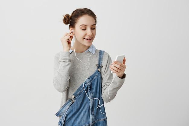 Mujer en overol de mezclilla estar relajado con smartphone viendo videos de internet. chica adulta escuchando música a través de auriculares con sonrisa. concepto de tecnología