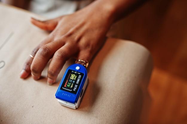 Mujer con oxímetro de pulso en la mano midiendo el nivel de saturación de oxígeno
