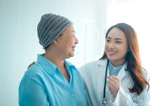 Una mujer paciente con cáncer con pañuelo en la cabeza después de la consulta de quimioterapia y médico visitante en el hospital