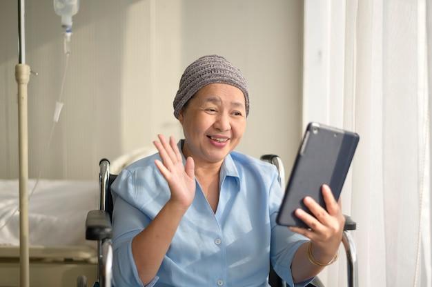 Una mujer paciente con cáncer con pañuelo en la cabeza haciendo videollamadas en la red social con familiares y amigos en el hospital.