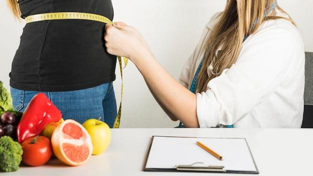 Mujer paciente de examen dietético en la clínica